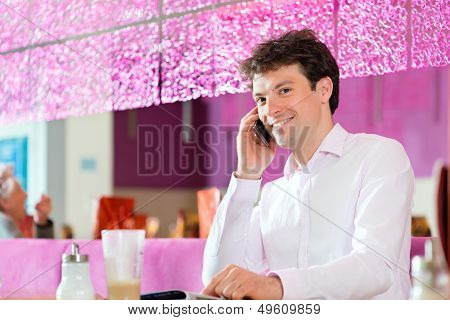 Young man in a cafe or ice cream parlor using his phone, maybe he is single or waiting for someone