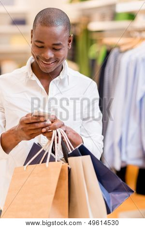 Shopping man texting on his phone at a store