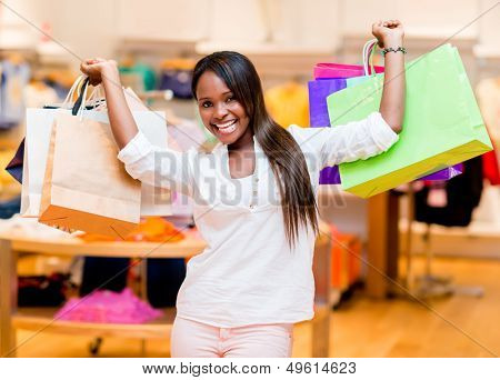 Excited shopping woman holding bags with arms up