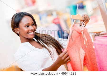 Happy shopping woman looking at clothes at a retail store