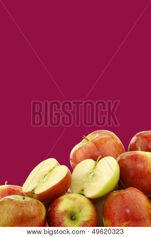 bunch of braeburn apples and a cut one on a dark red background