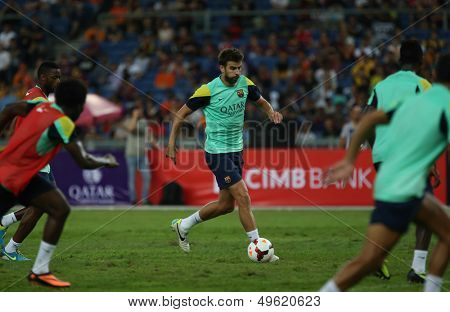 KUALA LUMPUR - AUGUST 9: FC Barcelona 's Gerard Pique dribbles the ball during training at the Bukit Jalil National Stadium on August 09, 2013 in Malaysia. FC Barcelona is on an Asia Tour to Malaysia.