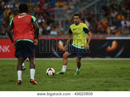 KUALA LUMPUR - AUGUST 9: FC Barcelona 's Xavi Hernandez (yellow bib) practices during training at the Bukit Jalil Stadium on August 09, 2013 in Malaysia. FC Barcelona is on an Asia Tour to Malaysia.
