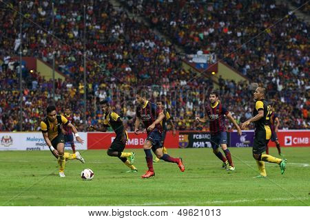 KUALA LUMPUR - AUGUST 10: FC Barcelona's Jordi Alba (red boots) leads in attack against the Malaysian team at the Shah Alam Stadium on August 10, 2013 in Malaysia. FC Barcelona wins 3-1.