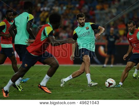 KUALA LUMPUR - AUGUST 9: FC Barcelona 's Gerard Pique controls the ball during training at the Bukit Jalil Stadium on August 09, 2013 in Malaysia. FC Barcelona is on an Asia Tour to Malaysia.
