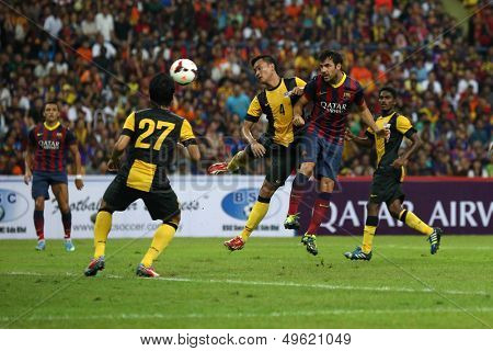 KUALA LUMPUR - AUGUST 10: Malaysia's Asraruddin (4) fails to stop FC Barcelona's Cesc Fabregas (maroon/blue) header goal at the Shah Alam Stadium on Aug 10, 2013 in Malaysia. FC Barcelona wins 3-1.