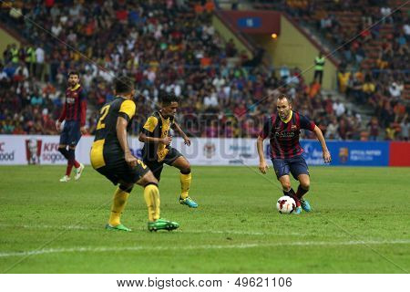 KUALA LUMPUR - AUGUST 10: FC Barcelona's Andres Iniesta (maroon/blue) controls the midfield in a game vs Malaysia at the Shah Alam Stadium on August 10, 2013 in Malaysia. FC Barcelona wins 3-1.