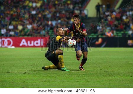 KUALA LUMPUR - AUGUST 10: FC Barcelona's Neymar (maroon/blue) takes on Malaysia's Mahalli Jasuli (yellow) at the Shah Alam Stadium on August 10, 2013 in Malaysia. FC Barcelona wins 3-1.