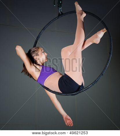 Beautiful woman gymnast performing aerial exercises