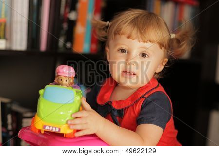 Little baby girl and her toy car