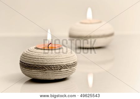 Tea light holders holding lit up candles spa concept