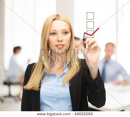 business and technology concept - businesswoman drawing checkmark on virtual screen