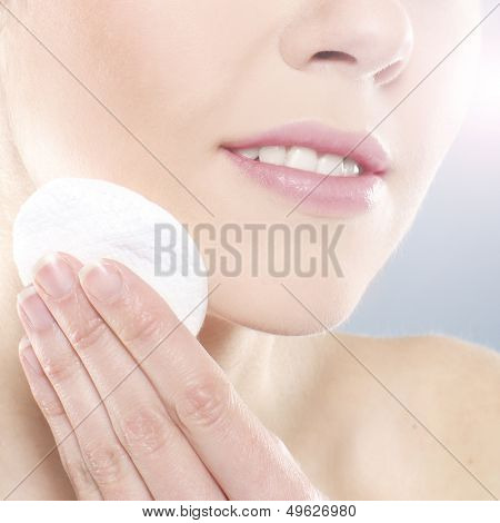 Beautiful and healthy young woman cleaning her face