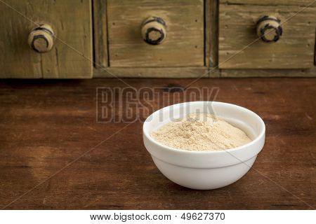 baobab fruit powder in a small bowl with a rustic drawer cabinet