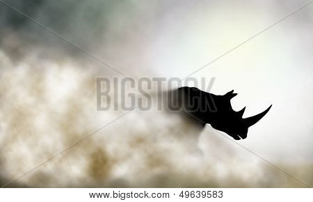 Editable vector illustration of a charging rhinoceros and dust cloud made using a gradient mesh
