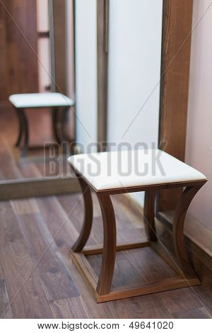 Low square stool with a padded seat in a modern interior decorated in wood