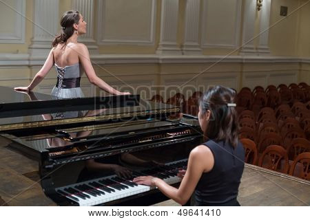 Woman pianist sits at the piano and beautiful singer stands next in empty concert hall