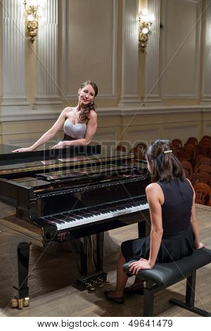 Woman pianist sits at the piano and beautiful singer stands next in concert hall