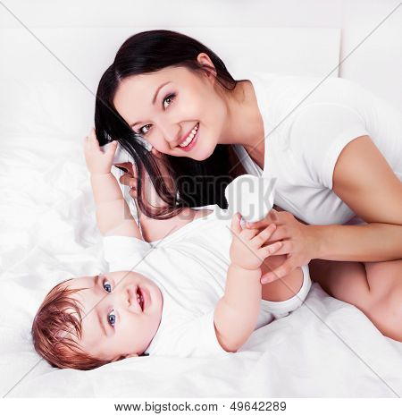 beautiful young mother with her baby in bed at home