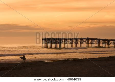 A Surfer Carrying His Surf Board From The Ocean At Sunset With Crystal Pier In The Background.