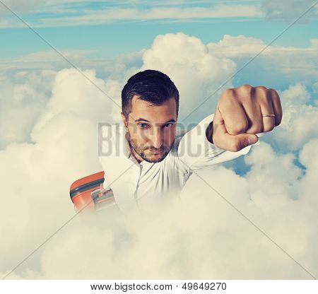 super hero businessman holding suitcase and flying through the clouds