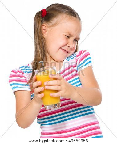 Little girl unwillingly drinking orange juice using straw, isolated over white