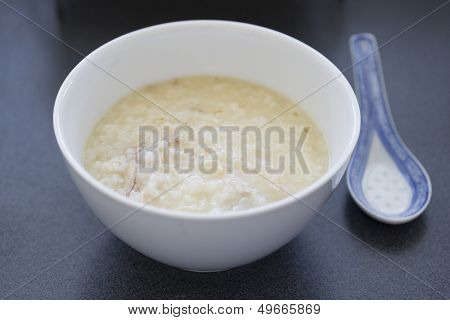Chinese rice porridge with chicken pieces in a white bowl with a spoon