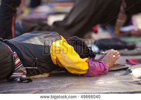 LHASA, TIBET-OCTOBER 08: Tibetan Buddhists pilgrim is praying in full ground prostration in front of the holy Jokhang Monastery on October 08, 2012 in Lhasa, Tibet.