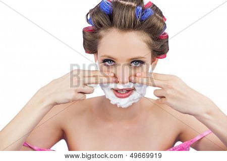Young model with fingers on face and shaving foam on white background