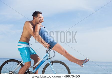 Man giving girlfriend a lift on his crossbar of bike on the beach