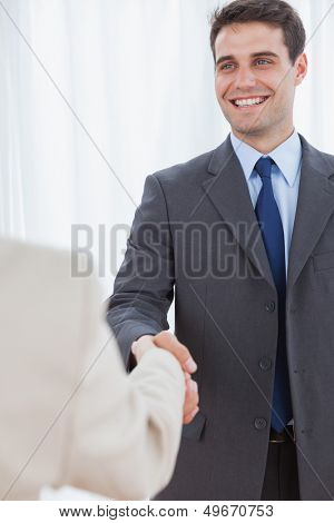 Cheerful businessman in bright office shaking hands with his new workmate