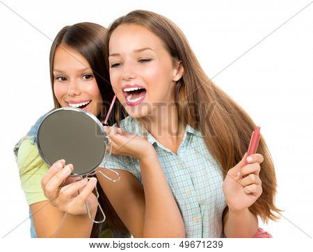 Teenage Girls Applying Make up and Looking in the Mirror. Pretty Teens Having Fun and Putting Makeup Lipstick or Lip gloss. Joyful Teenagers Isolated on a White Background. Cosmetic