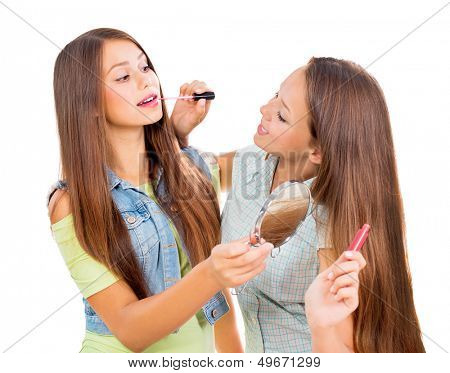 Teenage Girls Applying Make up and Looking in the Mirror. Pretty Teens Having Fun and Putting Makeup Lipstick or Lip gloss. Joyful Teenagers Isolated on a White Background. Cosmetics