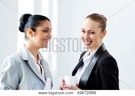 Image of two young pretty businesswomen smiling