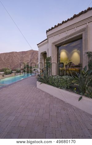 Paved poolside area and window exteriors of home against mountain and clear sky
