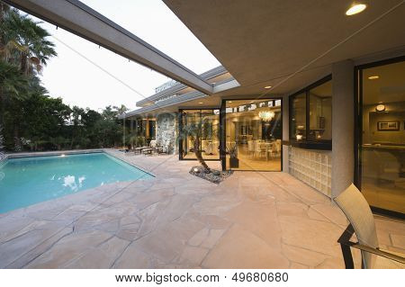 View of swimming pool and illuminated modern home exterior