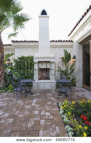 Chairs and tables at outdoor fireplace in courtyard garden of home