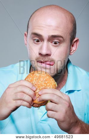 Funny man eating hamburger on grey background