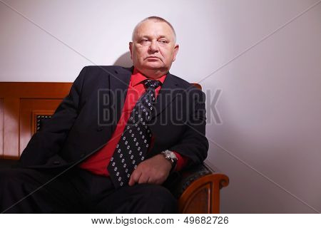 Serious senior businessman in black suit sitting on leather sofa in office