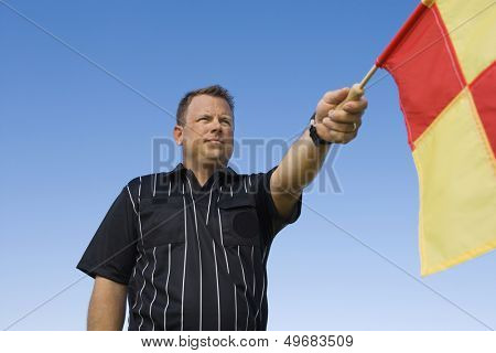 Low angle view of linesman showing penalty flag against clear blue sky