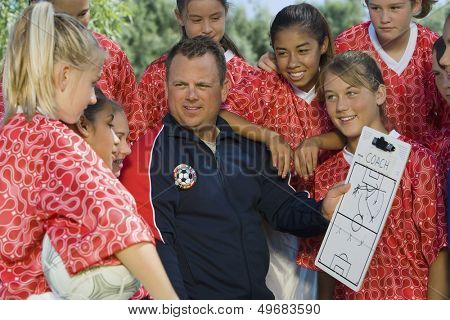 Coach holding clipboard while discussing strategy with girls soccer team