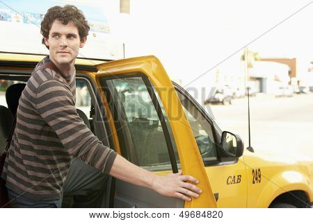Young man disembarking taxi while looking away