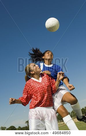 Girls heading soccer ball during match against blue sky