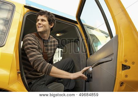 Low angle view of happy young man disembarking taxi