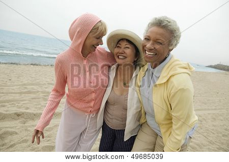 Portrait of happy middle aged female friends enjoying vacation at beach