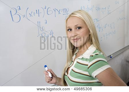 Closeup portrait of beautiful young student solving algebra equation on whiteboard in classroom
