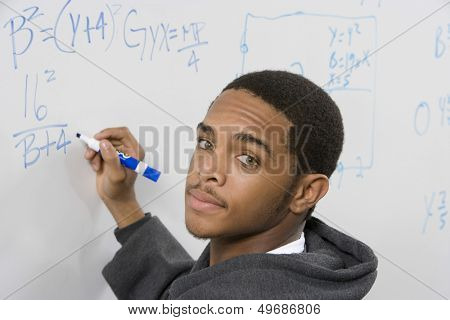 Closeup portrait of male student solving algebra equation on whiteboard in classroom