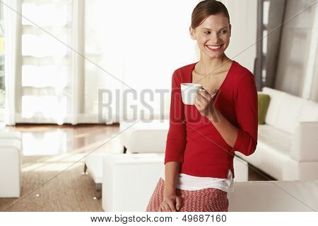 Thoughtful young businesswoman holding coffee cup in office lobby