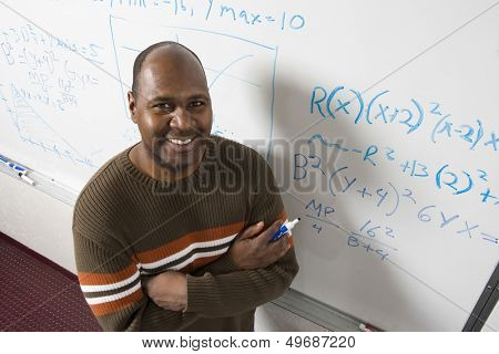High angle portrait of confident teacher solving math's equations on whiteboard in classroom
