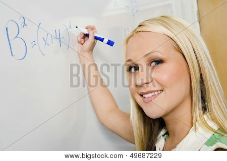 Closeup portrait of beautiful student solving algebra equation on whiteboard in classroom